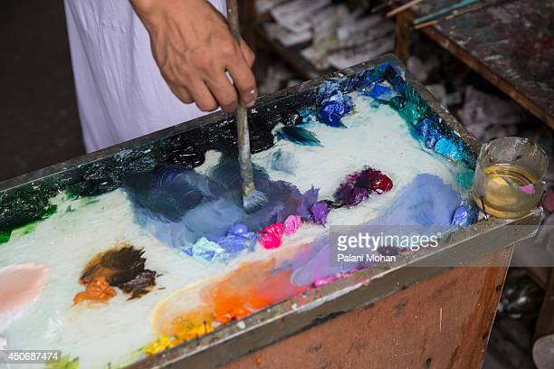 An artist blends colours on his palette in one of the workshops at the artist village on June 11 2014 in Shenzhen China The Dafen Artist Village in...