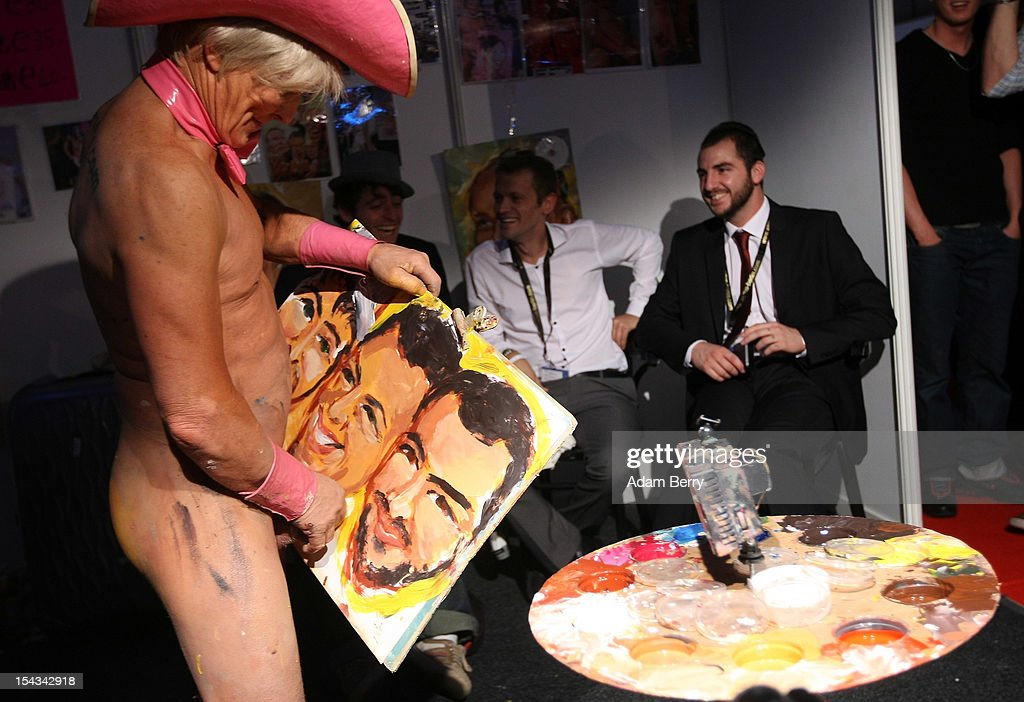 An artist calling himself 'Pricasso' paints a portrait of three men with his penis at the 2012 Venus Erotic Fair at Messe Berlin on October 18, 2012 in Berlin, Germany. The trade fair for the adult entertainment industry will be open from October 18 through 21.