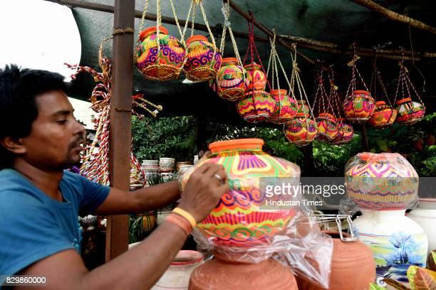 An artist checks a decorative earthern pots ahead of Dahi Handi Festival at Vashi on August 10 2017 in Mumbai India Dahi Handi is one of the festive...