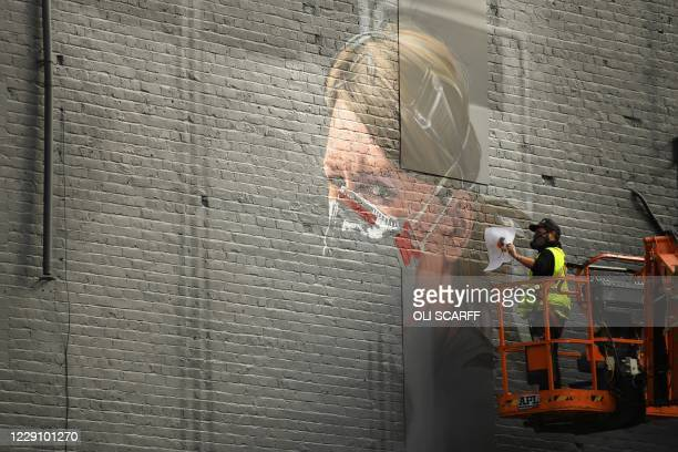 An artist creates a mural of a NHS worker on a wall in north Manchester on October 16 as the number of cases of the novel coronavirus COVID-19 rises....