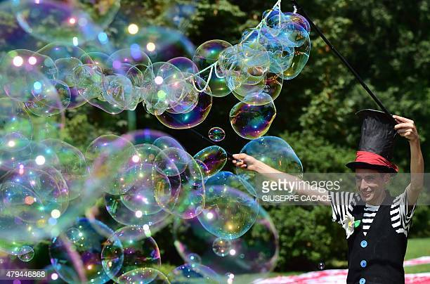 An artist creats soap bubbles in Parco Sempione in Milan on July 4 2015 as a major heatwave spreads throughout Europe with temperatures hitting...