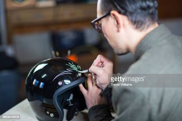 An artist customizing a motorcycle helmet and painting it by hand