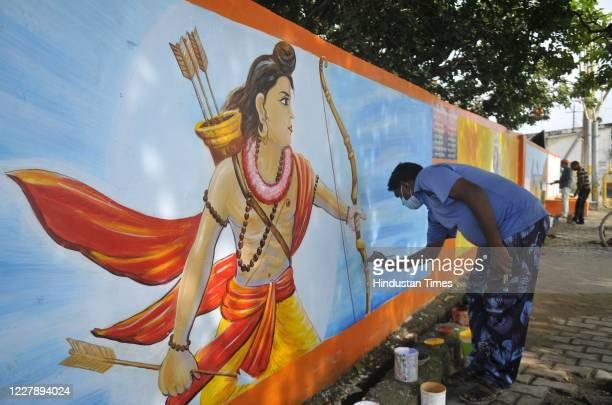 An artist decorates a wall of Karsevak Puram with a mural of the Hindu God Rama as part of preparation work for the foundation stone laying ceremony...