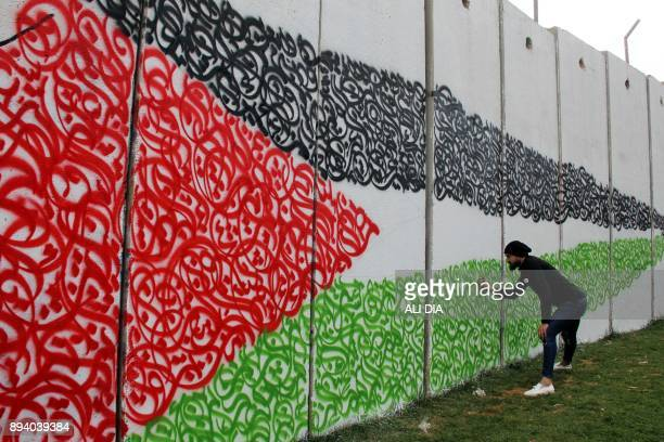 An artist draws the Palestinian flag on a wall on the southern Lebanese border with Israel near Fatima's Gate on December 17 in response to the...
