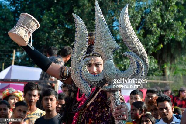 An artist dressed as Lord Shiva dances as others devotees immerse an idol of the Hindu goddess Durga in the waters of Mahananda river during the...