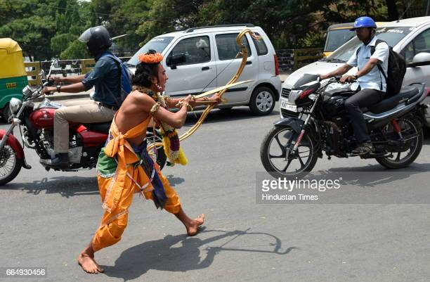 An artist dressed like the character of Ramayana performing amid traffic during a road show on the occasion of 9th day of Navratri at a Hanuman...
