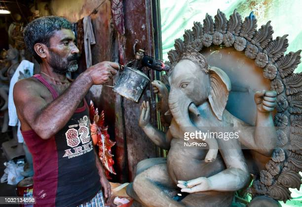 An artist fire an idol of Lord Ganesha to dry faster before colouring at a studio on the eve of Ganesh Chuturthi festival in Guwahati Assam India on...