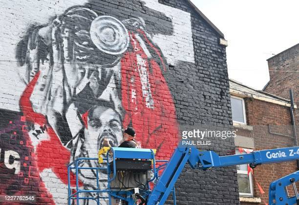 An artist from graffiti artists MurWalls in collaboration with The Redmen TV independent Liverpool FC media works on a new mural of Liverpool's...