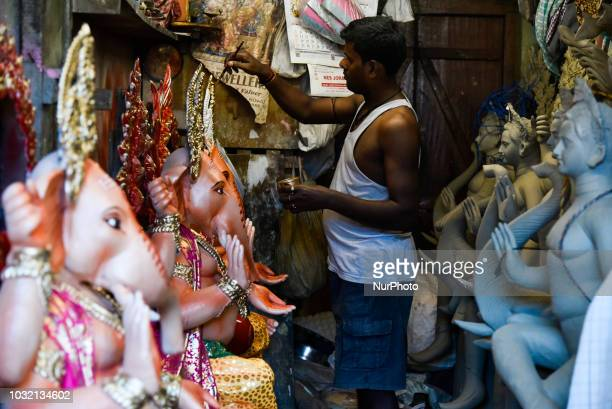 An artist gives finishing touches on an idol of Lord Ganesha at a studio on the eve of Ganesh Chuturthi festival in Guwahati Assam India on Wednesday...