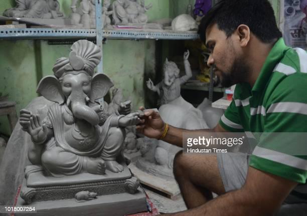 An artist making ecofriendly Ganesh Idols for the upcoming Ganapti Festival at Kumbharwada in Kalyan West on August 16 2018 in Mumbai India Photo by...