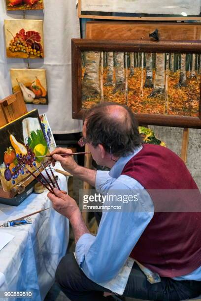 an artist making finishing touches on a drawing. - emreturanphoto stock pictures, royalty-free photos & images