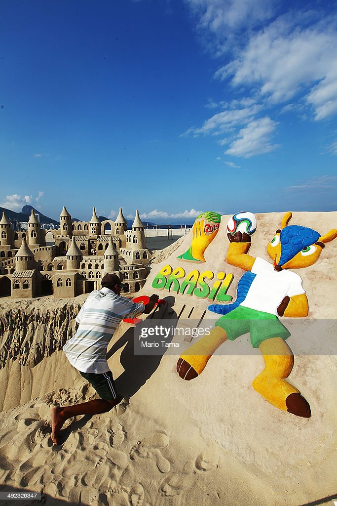An artist paints a 2014 World Cup design on a sand castle on Copacabana Beach on May 19, 2014 in Rio de Janeiro, Brazil. Brazil is gearing up to host 600,000 foreign tourists for the 2014 FIFA World Cup which kicks off June 12.