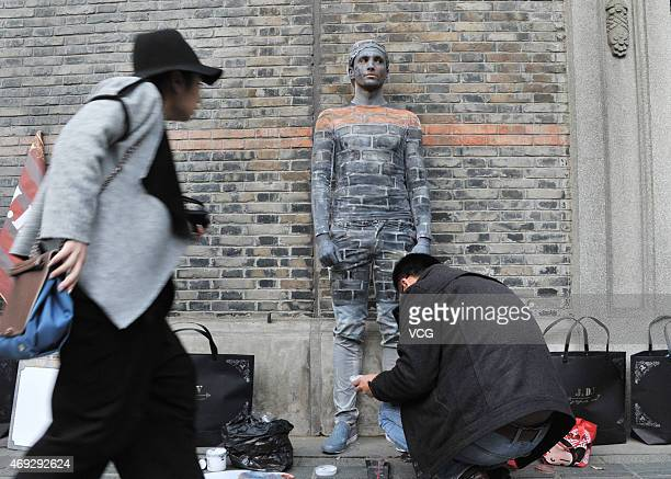 "An artist paints a boy disguised as a wall near New World street on April 10, 2015 in Shanghai, China. A boy ""hides"" himself by being painted the..."