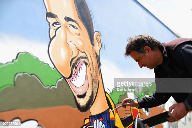 An artist paints a Daniel Ricciardo of Australia and Red Bull Racing mural in the fan area during the Spanish Formula One Grand Prix at Circuit de...