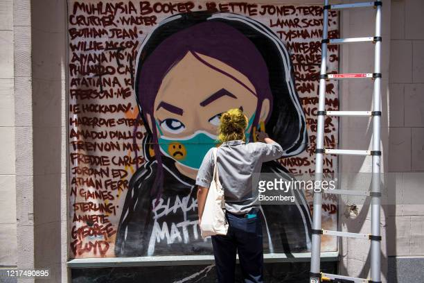 An artist paints a mural on a piece of plywood attached to a storefront window in Oakland, California, U.S., on Wednesday, June 3, 2020. In the past...