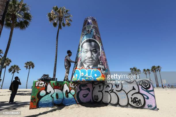 An artist paints graffiti near an image of Dr. Martin Luther King Jr. At the closed and mostly empty Venice Beach, amid the COVID-19 pandemic on...