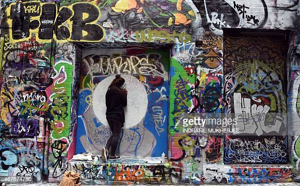 An artist paints graffiti on a wall inside Rutledge Lane in Melbourne on March 26 2015 Hosier and Rutledge Lane off Flinders street is a much...