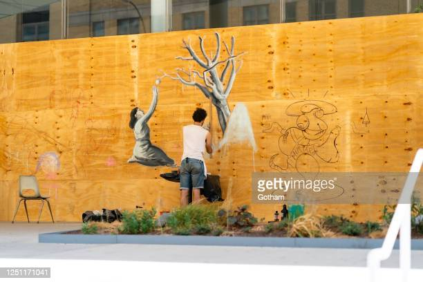 An artist paints on the boarded-up windows of the Whitney Museum of American Art in the Meatpacking District on June 21, 2020 in New York City.