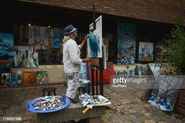 An artist paints on the main street in BeuvronenAuge On Friday August 2 in Caen Normandy France