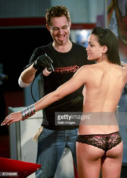 An artist performs body art on a woman at the Cape Town Sexpo on May 14, 2009 in Cape Town, South Africa. The Sexpo is the world's largest health,...