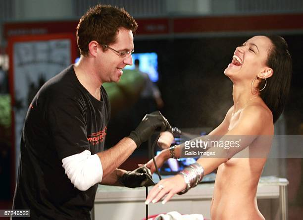 An artist performs body art on a woman at the Cape Town Sexpo on May 14 2009 in Cape Town South Africa The Sexpo is the world's largest health...