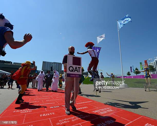 An artist performs on jumping stilts on July 23 2012 as members of the Qatar delegation arrive for the Flag Raising ceremony at the Olympic Village...