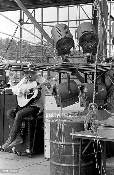 An artist plays guitar backstage at the Woodstock Music Festival Bethel NY August 15 1969