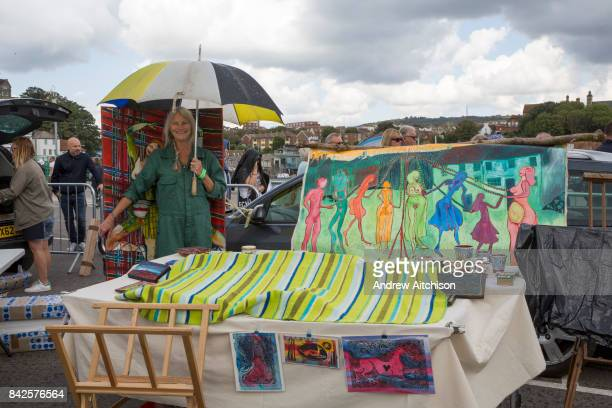 An artist protects her work with a blanket and umbrella from the rain during the 2017 Art Car Boot Fair Folkestone Kent