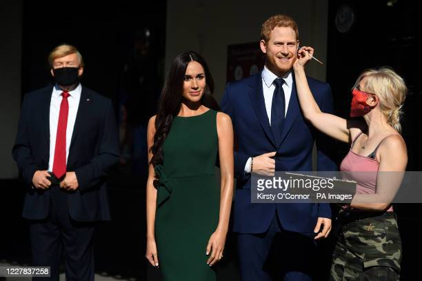 An artist puts the finishing touches the wax figures of the Duke and Duchess of Sussex in the entrance line at Madame Tussaud's in London as the...