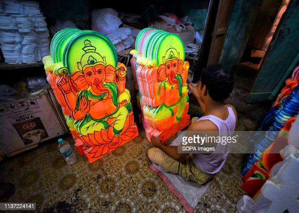 An Artist seen giving a final touch on different decorative items of Lord Ganesha Swastika symbol which will be used for Poila Baisakh ahead of the...