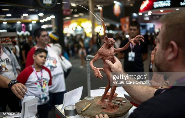 An artist shapes a character out of clay at Sao Paulo Comic Con 2017 in Brazil on December 7 2017 The annual edition of Sao Paulo Comic Con is taking...