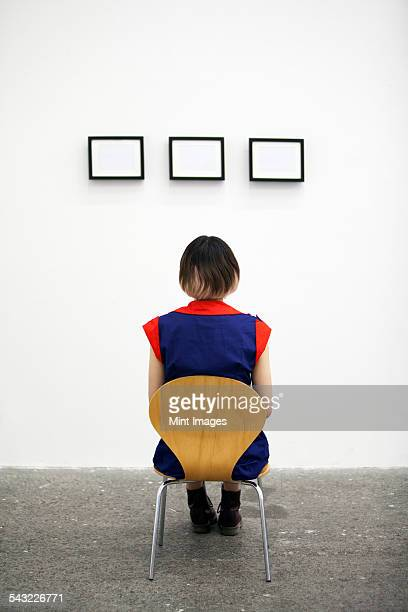 An artist sitting on a chair, looking at an artwork.