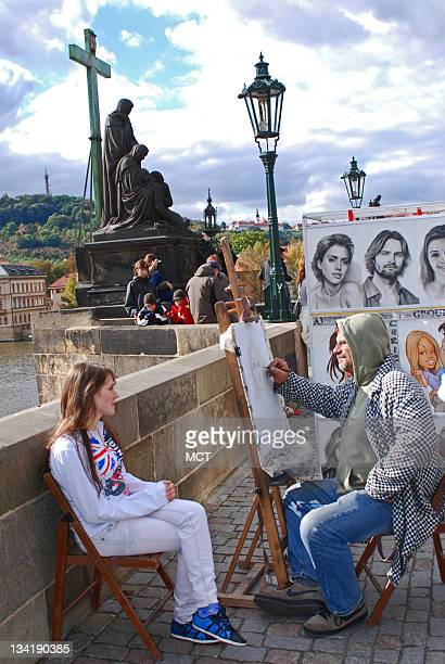 An artist sketches along the Charles Bridge in Prague