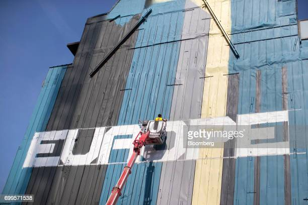 An artist stands on a cherry picker to work on a mural next to the European commission and the Europa building in Brussels, Belgium, on Thursday,...