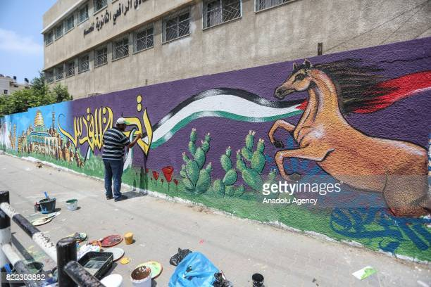 An artist works on a mural painting drawn to visualize Palestinians exposure to Israel's violations on Jerusalem and AlAqsa Mosque Compound by a...