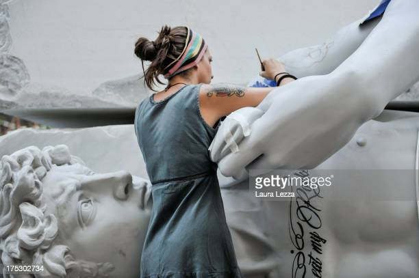 An artist works on a tattooed copy of Michelangelo's statue of David during the Carrara Marble Weeks 2013 on August 1 2013 in Carrara Italy The Group...