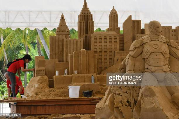 An artist works on her sand sculpture ahead of the Sentosa Sansation Festival at Siloso beach in Sentosa island resort in Singapore on August 27 2018...