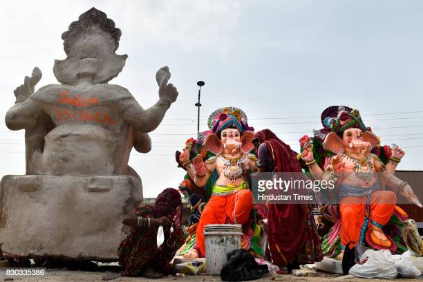 An artist works on the idol of elephantheaded Hindu God Ganesha being prepared for Ganesh Chaturthi festival at a workshop on August 11 2017 in New...