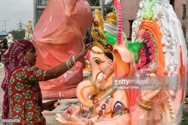 An artist works on the idol of elephantheaded Hindu God Ganesha which is being prepared for Ganesh Chaturthi festival at a workshop on August 11 2017...