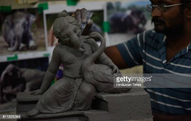 An artist works on the idol of Ganesha at a workshop at Lower Parel on July 8 2017 in Mumbai India