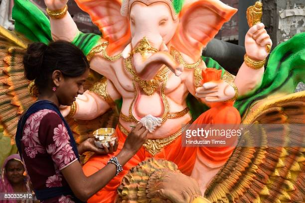 An artist works on the idols of elephantheaded Hindu God Ganesha which is being prepared for Ganesh Chaturthi festival at a workshop on August 11...