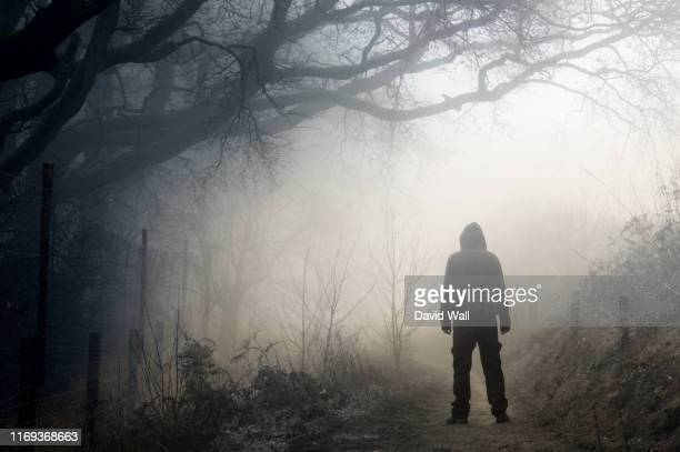 an artistic double exposure of a lone hooded figure on a path in the countryside on a spooky, foggy winters day. - evil stock pictures, royalty-free photos & images