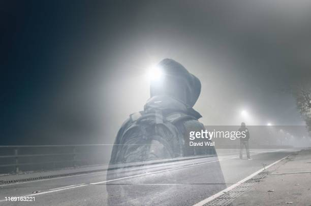an artistic double exposure of a lone hooded figure standing in the middle of a country road below a street light on a spooky night. - mystery stock pictures, royalty-free photos & images