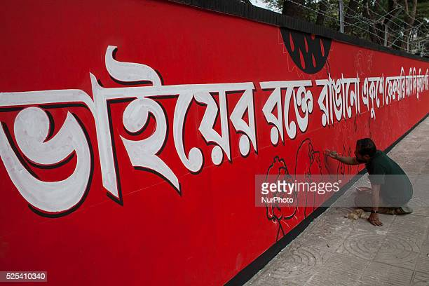 An artistpainting on a wall in front of the Shaheed Minar the Language Movement Memorial in Dhaka on February 20 2015 as a part of preparations for...