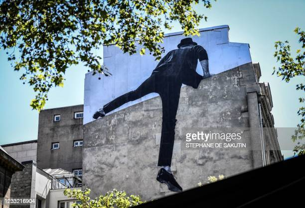 An artwork by French street artist and photographer Jean Rene, aka JR, is displayed on a building in Paris, on June 1, 2021. - - RESTRICTED TO...