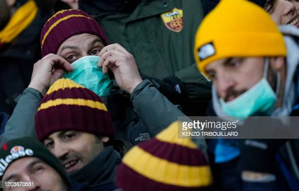 An AS Roma supporter wearing protective face mask prior the UEFA Europa League round of 32 second leg football match between KAA Gent and AS Roma on...