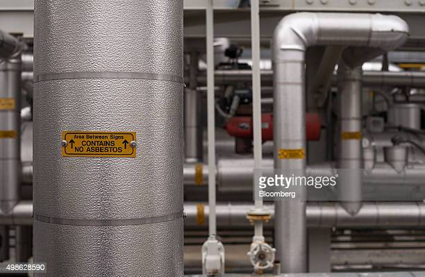 An asbestos warning sigh is displayed on pipes that run in and out of the heat recovery steam generator at the American Electric Power Appalachian...