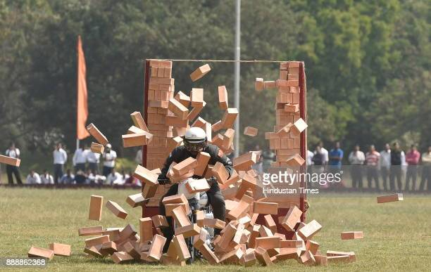 An ASC 'Tornadoes' personnel rides past through the wall of bricks during the celebration of 257th Corps Day of Army Service Corps at Agram ground on...