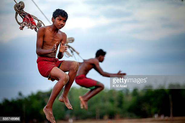 An ascetic devotee hangs from a spinning wheel attached with Charak Tree to celebrate the rituals of Charak Puja also known as Nil Puja in Sylhet...
