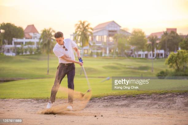 an asia mature golfer hit the ball in the sand. - chip shot stock pictures, royalty-free photos & images